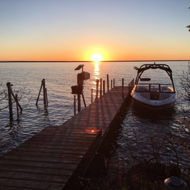 Sunset on lake by boat dock with boat