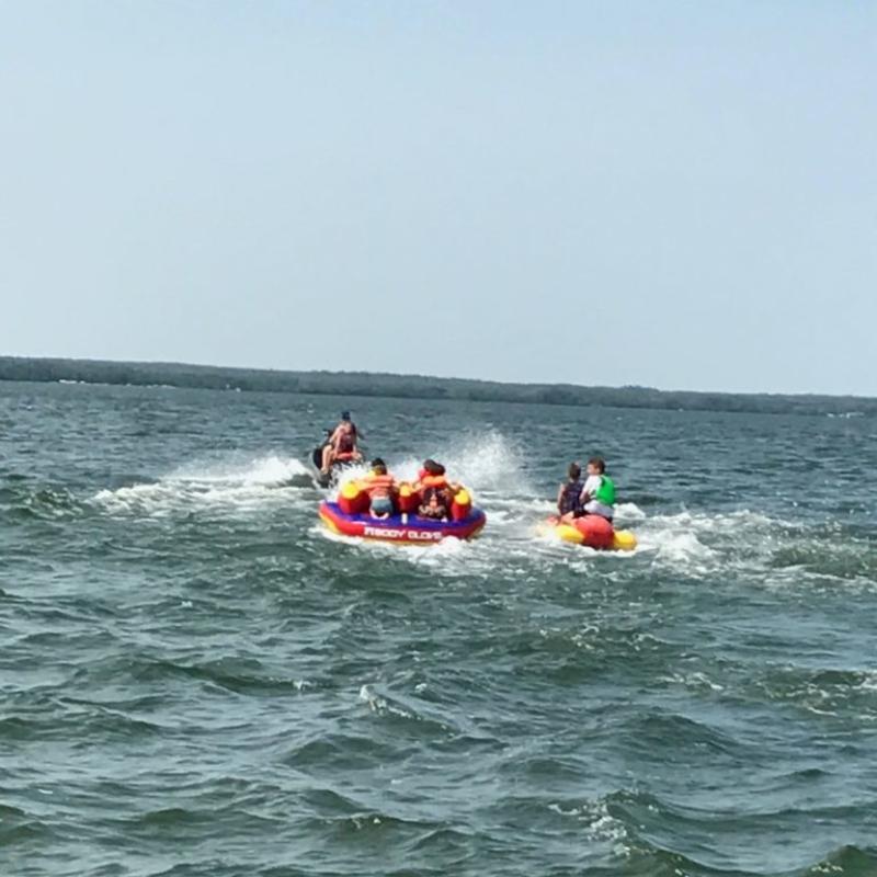 People in water being pulled on tube behind jetski